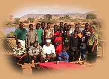 Camp staff with the Orphans around the breakfast table with the Galana River in the background.